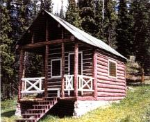 Corner view of Medicine Tent Warden Cabin, showing its log-framed sheltered porch area at the entrance gable, 1996.; Parks Canada Agency / Agence Parcs Canada, 1996.