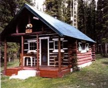 General view of Rocky Forks Warden Cabin showing its log-framed sheltered porch area at the entrance gable.; Agence Parcs Canada / Parks Canada Agency, 1996.