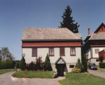 View of the exterior of the Potting Shed, showing the shingled flared apron on the second floor, 1995.; Parks Canada Agency / Agence Parcs Canada, 1995.