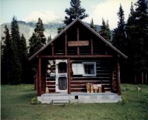 Front elevation of the Adolphus Warden Patrol Cabin, showing its log-framed open porch with trussed-purlin supports and posts at the gable end, 1997.; Parks Canada Agency / Agence Parcs Canada, 1997.
