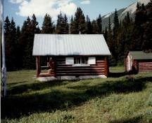 Side view of the Adolphus Warden Patrol Cabin, showing its walls of peeled logs, horizontally laid and saddle-notched at the corners, 1997.; Parks Canada Agency / Agence Parcs Canada, 1997.