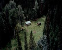 Aerial view of Middle Forks Warden Patrol Cabin, showing the cabin, the clearing, adjacent shed, and the surrounding forest, 1997.; Parks Canada Agency / Agence Parcs Canada, 1997.