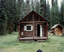 View of the main entrance to the Middle Forks Warden Patrol Cabin, showing the rustic architecture practiced within National Parks, 1997.; Parks Canada Agency / Agence Parcs Canada, 1997.