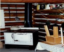 Interior view of the Middle Forks Warden Patrol Cabin, showing the interior objects and its walls constructed of peeled logs, 1997.; Parks Canada Agency / Agence Parcs Canada,  1997.