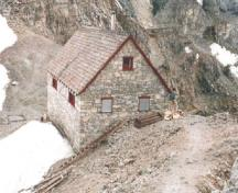 Corner view of Abbot Pass Refuge Cabin, showing the rear and side elevations, 1986.; Agence Parcs Canada, Direction des services historiques / Parks Canada Agency, Historical Services Branch, Rick Stuart, 1986.