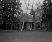 General view of the Golf Clubhouse, showing the peeled log construction walls and extensive stone detailing, 1986.; Parks Canada Agency / Agence Parcs Canada, Mills, 1986.