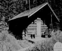 General view of the Bunkhouse, showing its simple massing as a single-room with a gable roof, extended on log purlins over the entrance to shelter the stoop, 1994.; Agence Parcs Canada / Parks Canada Agency, 1994.