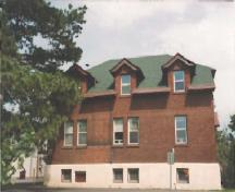 Side facade of the Arc Biotech Building (No.34); showing the subtle brick coursing pattern on the red brick walls, painted wood trim and the high concrete foundation, 1999.; Agence Parcs Canada / Parks Canada Agency, 1999.