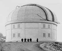 Side view of the Dominion Astrophysical Observatory showing its simple cylindrical massing with dome.; Parks Canada Agency / Agence Parcs Canada, Andrew Waldron.