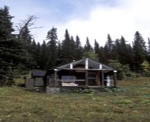 View of the exterior of the Floe Lake Warden Patrol Cabin, showing the simple, well-proportioned composition of this rectangular building which features a medium-pitched gable roof, 2005; Parks Canada Agency / Agence Parcs Canada, C. Siddal, 2005.