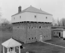 Corner view of the Blockhouse, showing the square, three-storey massing with pyramidal roof, and the chimneys, 1991.; Parks Canada Agency / Agence Parcs Canada, 1991.