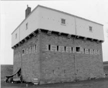 Corner view of the Blockhouse, showing the centrally placed gun ports of the second floor, each flanked by four single-rifle loopholes trimmed with lighter coloured stonework, 1991.; Parks Canada Agency / Agence Parcs Canada, 1991.