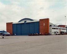 General view of Hangar 2 demonstrating the high, wide doorways that span its east and west elevations, the raised central sections for particularly high aircraft, and the brick pylons at each end, 2000.; Department of National Defence / Ministère de la Défense nationale, 2000.