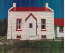 Front view of the Old Dwelling, Cove Island, demonstrating the whitewashed exterior walls of rough faced, rusticated stone set in even courses, with a slightly projecting basement course, 1990.; Canadian Coast Guard/Garde côtière canadienne, 1990.