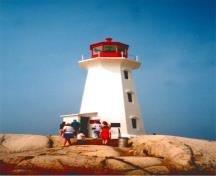 General view of Peggy's Cove lighthouse, showing the octagonal shape, elegantly curved cornice and stylized window caps which reflect a modern aesthetic, 2001.; Department of Fisheries & Oceans Canada/Département de pêches et océans Canada, 2001.