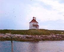 Panoramic view of Rook Island from the north demonstrating the building's distinctive, isolated silhouette, which is visible from the mainland and all points in the harbour, reinforces the lighthouse's landmark and symbolic value to the community, 2001.; Department of Fisheries & Oceans Canada/Département de pêches et océans Canada, 2001.