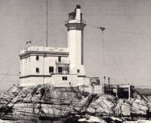 General view of the exterior of the Light Tower, showing its form and massing which consist of a tall, slightly tapered octagonal tower with narrow slit openings, flared lantern platform, lantern and light.; Parks Canada Agency / Agence Parcs Canada