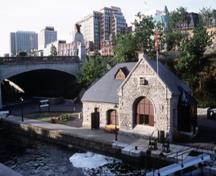 View of the principal entrance of the Lock Office, showing its Romanesque Revival elements, such as thick voussoirs and a large semi-circular arch, 2002.; Parks Canada Agency / Agence Parcs Canada, A. Guindon, 2002.