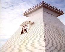 Detail view of the Mabou Lighthouse showing the classical proportions and detailing including the pedimented window and door openings, six-over-six sash windows and cornice, 2002.; Public Works Canada / Ministère des Travaux publics, 2002.