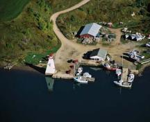 Aerial View of Mabou Lighthouse and wharf putting an emphasis on its symbolic value to the communities of Mabou Harbour as a reminder of the dependence of the area on ocean-based activities, 2001.; Department of Fisheries & Oceans Canada/Département de pêches et océans Canada, 2001.