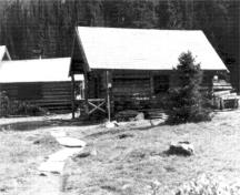 General view of the Elizabeth Parker Hut (left) and Wiwaxy Lodge (right)showing the simple massing of the rectangular building and pitched roof with a generous overhang, 1987.; Public Works Canada / Ministère des Travaux publics, A. Powter, 1987