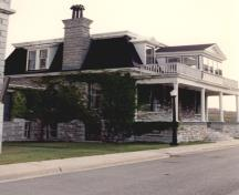View of the front entrance of RMC Building 55, showing the prominent main elevation, with its broad and high porch, columns and stone staircase, 1993.; Parks Canada Agency / Agence Parcs Canada, 1993.