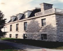 View of the side of RMC Building 55, showing the continuous stone string course and wall surfaces, and the eave mouldings, 1993.; Parks Canada Agency / Agence Parcs Canada, 1993.