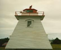Side elevation of the Tower, showing the low, square massing and profile comprised of a tapered shaft with a square wooden gallery and octagonal lantern, 1990.; Canadian Coast Guard / Garde côtière canadienne, 1990.