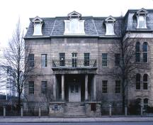 Facade of the Bank of Upper Canada Building showing the Neoclassical portico, consisting of: a raised podium; paired columns; a strongly defined entablature; and a second-storey balcony.; Parks Canada \ Parcs Canada, n.d.