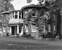 Corner view of the Fairholm villa showing the mottled red brick walls; and cut stone used as lintels over the windows, for the raised basement, and as a string course between the two storeys.; Parks Canada Agency / Agence Parcs Canada, n.d.