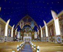 View of the interior of the Church of Our Lady of Good Hope emphasizing the Gothic style painted decoration of interior, including ornamentation surrounding figural panels and ornamented wainscotting, painted floor, painted tripartite arch motif at altar.; Parks Canada Agency / Agence Parcs Canada, n.d.
