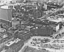 Historic image of an aerial view over the Halifax Waterfront Buildings emphasizing the spatial relationship of the buildings to each other and to the harbour.; Parks Canada Agency / Agence Parcs Canada, n.d.