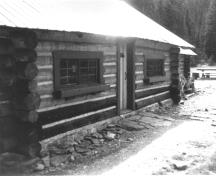 Exterior photograph showing the horizontally laid, peeled round logs with saddle-notched corners.; Parks Canada