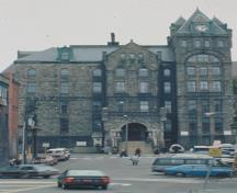 Front facade of St. John's Court House showing the three-storey, Duckworth Street facade, characterized by a central projecting bay with arched entrance, a series of blind arches, a square tower at one corner, and a massive round tower at the other.; Parks Canada/Parc Canada, n.d.