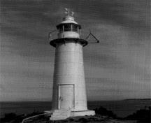 General view of the lighttower at King's Cove Head, showing the simple massing of the tower which consists of a smooth tubular form composed of a base, shaft, lantern platform and lantern with a lantern cap and prominent weathervane, 1989.; Canadian Coast Guard/Garde côtière canadienne, 1989.