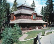General view showing the stepped massing defined by the wide bracketed veranda, hipped roof form of the main block, and the lantern set at the top of the roof.; Parks Canada