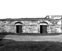 Front facade of the North Front Casemate showing the simple composition of a central door flanked by two side windows, 1989.; Parks Canada Agency / Agence Parcs Canada, 1989.