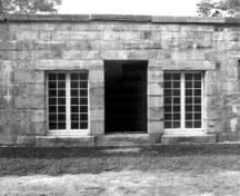 Front facade of the West Front casemates portraying its simple, unadorned stone façade, with a door flanked by two side windows, 1989.; Parks Canada Agency / Agence Parcs Canada, 1989.