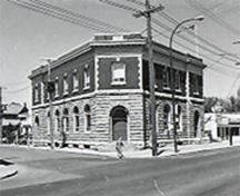 "General view of Postal Station ""B,"" showing the classical order of the symmetrical façades that includes the rusticated stone first floor, the brick second floor, and a projecting metal cornice and brick parapet trimmed in stone, 1971.; Canadian Inventory of Historic Buildings/Inventaire des Bâtiments Historiques du Canada, 1971."