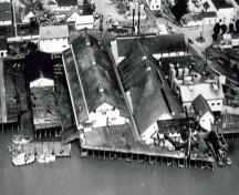 Aerial view of its siting, built on wharf structures out over the river.; Parks Canada Agency / Agence Parcs Canada