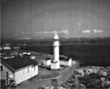 General view of the Channel Head Lighttower, showing the smooth tubular construction and overall utilitarian appearance of the structure in its setting among the only structures on a small island, 1987.; Canadian Coast Guard/Garde côtière canadienne, 1987.