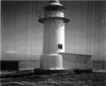 General view of the Channel Head Lighttower, showing the cylindrical massing of the tower consisting of several cylindrical segments and a small wood frame lean-to at its base, 1987.; Canadian Coast Guard/Garde côtière canadienne, 1987.