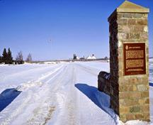 General view of the main entrance to Fort Battleford National Historic Site of Canada showing the Historical Sites and Monuments Board of Canada plaque and depicting the fort in the background, 1991.; Parks Canada Agency / Agence Parcs Canada, D. McArthur, 1991.