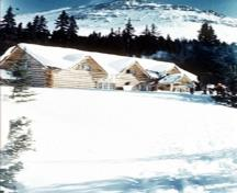 General view of the Skoki Ski Lodge showing its simple configuration, horizontal log construction with locally cut, unscribed, spruce logs, joined with saddle- or dovetail-notched corners, 1959.; Parks Canada Agency / Agence Parcs Canada, 1959