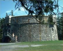 General view of the Prince of Wales Tower, showing the squat, massing tower, 1993.; Parks Canada Agency/ Agence Parcs Canada, 1993.