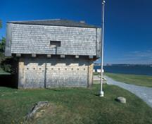 Side view of the St. Andrews Blockhouse, showing its tripartite design with squat lower storey, overhanging upper storey, and pyramidal roof, 2003.; Parks Canada Agency/Agence Parcs Canada, B. Townsend, 2003.