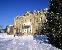 General view of the Old Government House National Historic Site of Canada showing the pedimented projecting frontispiece with semi-circular portico over the main entry, 1995.; Parks Canada Agency / Agence Parcs Canada, J. Butterill, 1995.