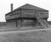 General view of Blockhouse 3, showing the squared logs with dovetailed corners, the loopholes, small windows and entrances on both levels, ca. 1989.; Parks Canada Agency / Agence Parcs Canada, ca. 1989.