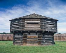 General view of the Octagonal Blockhouse showing the exterior walls constructed of squared logs with dovetailed corners, and the loopholes, 1978.; Agence Parcs Canada / Parks Canada Agency, T. Grant, 1978.
