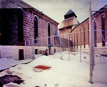 General view of the main cellblock at Saint-Vincent-de-Paul Penitentiary showing the high, surrounding stone wall which provides the distinctive public face of the institution.; Parks Canada Agency / Agence Parcs Canada, n.d.